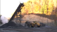 Frontend loader truck working below elevated conveyor chute moving coal from one pile to another mountain trees BG Mining operation Appalachian...