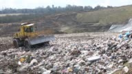 A frontloader bulldozer made by Bomag moves nonrecyclable rubbish across a landfill waste site operated by Biffa Group Ltd near Redhill / A truck...