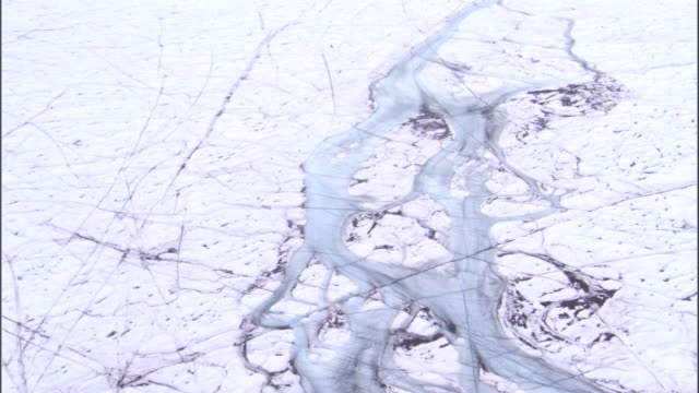 Frozen bodies of water wind through an ice field in Greenland. Available in HD.
