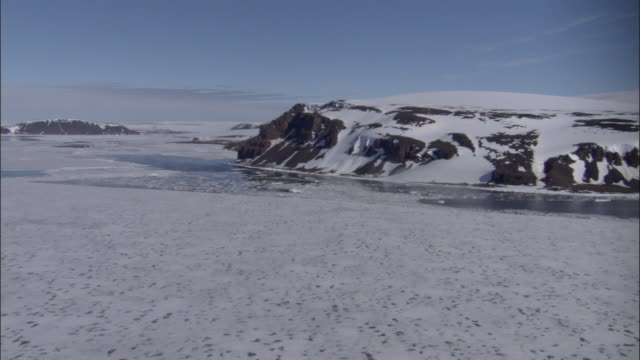 LOW AERIAL, Frozen sea and rock formations, Cape Mill, Franz Josef Land, Russia