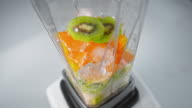SLO MO Fruit and ice cubes being mixed in the blender
