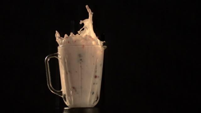 Fruit and milk flying out of blender (slow motion)