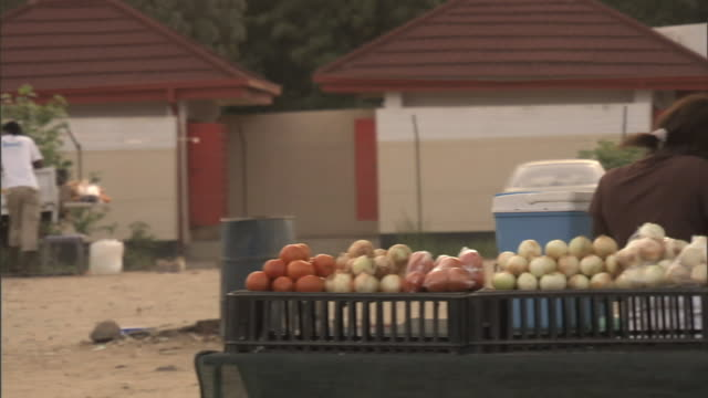 Fruit vegetable stand on side of road various unidentifiable African people around parked cars BG