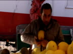 Fruiterer stuffs melons into jacket as pseudo breasts during comedy sales pitch at market stall Hamburg