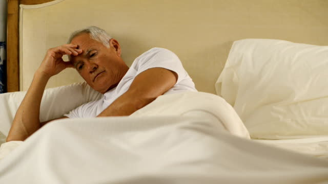 Frustriert und ein deprimierter Mann im Bett