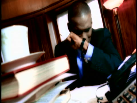 CANTED frustrated Black businessman pounding fist on desk + burying face in arms