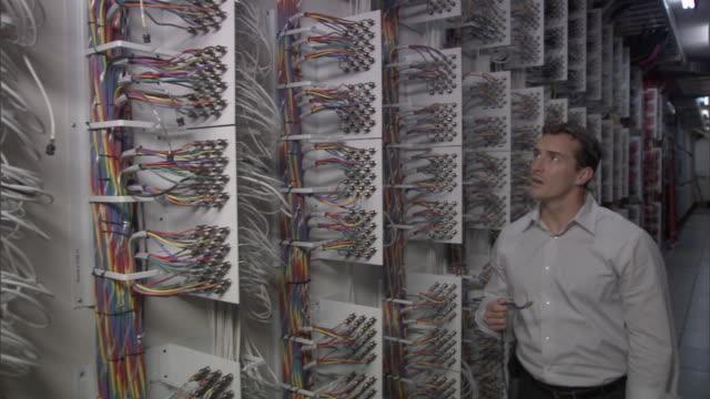 MS Frustrated businessman walking through computer server room / Culver City, California, USA