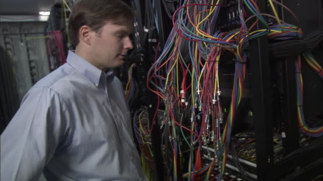 MS Frustrated businessman working on cables in computer server room / Culver City, California, USA
