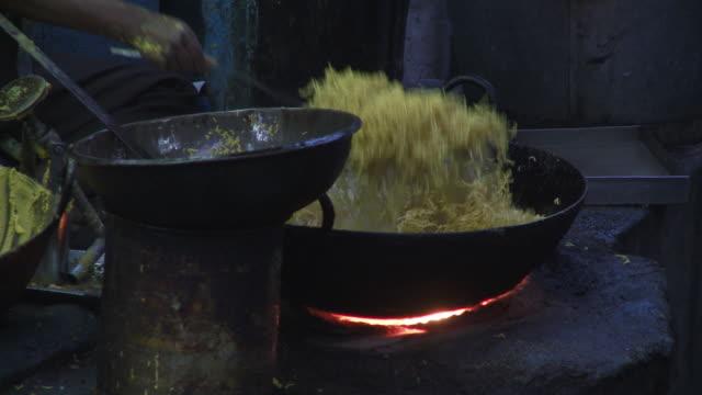 Frying noodles in big metal pan over flame