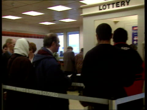 Long queue of punters queuing for first lottery rollover jackpot PAN CMS Man holding ticket as another holds bundle of 10 pound notes next