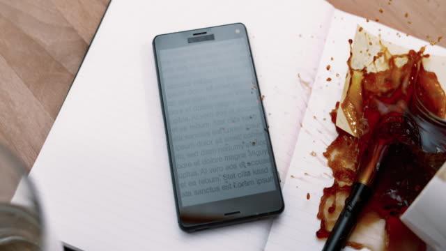 SLO MO LD A full cup uit koffie morsen op een mobiele telefoon en een laptop op de tafel