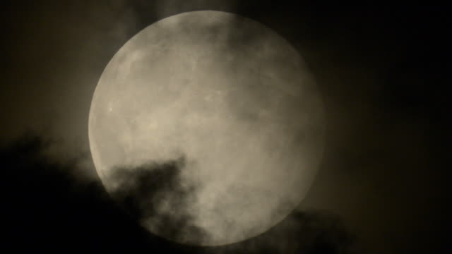 full moon behind dark clouds