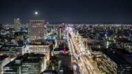 TL, WS Full moon rising over central Osaka at night / Osaka, Japan