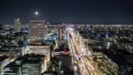 TL, WS Full moon rising over central Osaka at night / Osaka, Japan