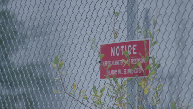Full shot of a no trespassing sign on a wire fence of an airport