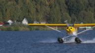 Full shot of a seaplane skimming across Lake Hood