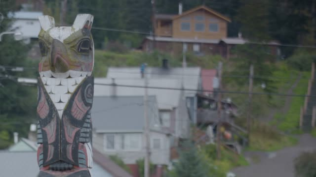 Full shot of a wooden owl sculpture with houses in the background