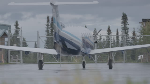 Full shot of an airplane parking by a wooden building at Iliamna airport