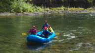 Full shot of four people rafting on a river