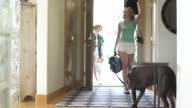 Full shot of group of friends arriving home and greeted by a dog