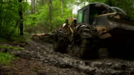Full shot of skidder as it drags trees through the mud, moving screen right, moving toward the camera, then away from the camera.