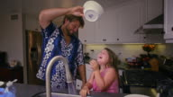 Fun and games father pours water on his daughter as they clean dishes together. Med