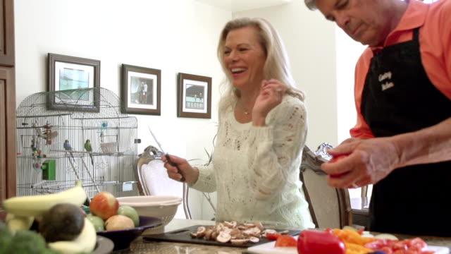 SLOW MOTION - Fun Mature Preparing Food in Kitchen.
