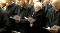 Funeral of Nat Lofthouse held in Bolton People in church standing and singing hymn from order of service carrying picture of Nat Lofthouse /...