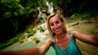 Funky woman takes selfie by the waterfalls