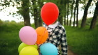 Funny male nerd playing with balloons