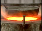 Furnace and molten gold closeup flames gold about to be poured and then the molten gold is poured into ingot trays Filmed at a now defunct gold mine...