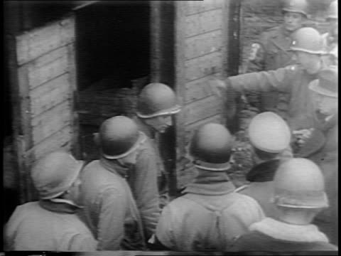 Furnace door opens to a charred body inside / bodies lie in a ditch / soldiers look through ditches of mass bodies / General Dwight D Eisenhower and...