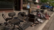 Furniture and musical instruments litter a street curb in the aftermath of a flood.