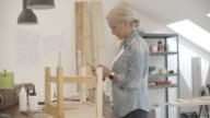 4K: Furniture Designer Using Smart Phone In Her Workshop.