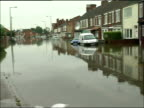 Further heavy rain and flood warnings ENGLAND South Yorkshire Bentley EXT Flooded suburban street Half submerged car men along past it in rowing boat