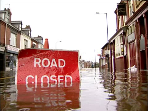 Further heavy rain and flood warnings 'Road Closed' sign half submerged in flooded street Man in waders along flooded street Sandbags in flood water