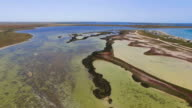 Futuristic landscape of salt marshes between lakes in summer, aerial video