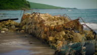 Gabion baskets act as sea defences on a Jamaican beach affected by erosion.