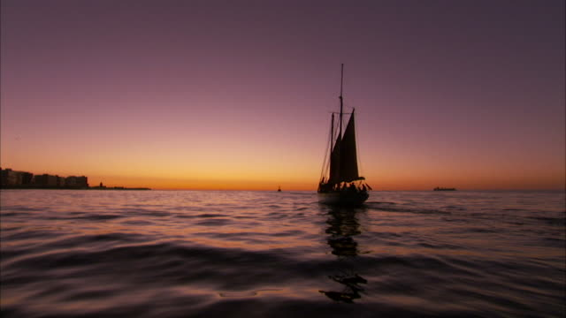 A gaff-rigged schooner sails towards the sunset. Available in HD