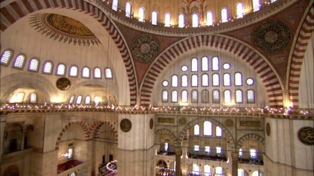 Galleries of windows and arches support the domed ceiling of the Suleymaniye mosque. Available in HD.
