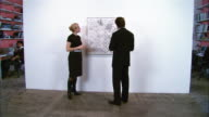 Gallerist discussing artwork with buyer at contemporary art gallery / man removing wallet to write check