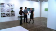 Gallery owner and artist looking at artwork off frame / greeting curator and looking at artwork on wall