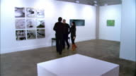 Gallery owner greeting couple and showing them panels of lily pads on view