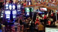 LS T/L gamblers crowded around blackjack tables in gambling casino with slot machines nearby / Las Vegas, Nevada, USA