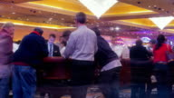 LA T/L gamblers leaning over crap tables gambling in casino  / Las Vegas, Nevada, USA