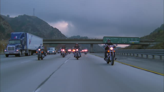 Gang of bikers on Harley Davidsons ride along freeway, California, USA Available in HD.