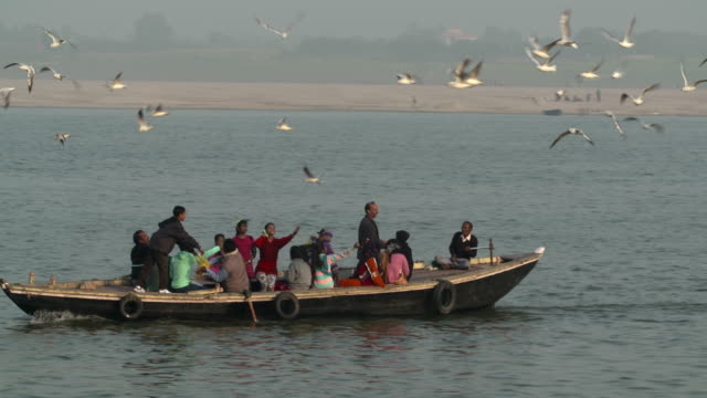 Ganges River Boatwith a family having good time feeding seagulls