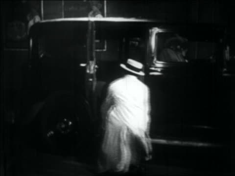 B/W 1934 gangster pushing other dead/wounded gangster into car then jumping in as it drives away