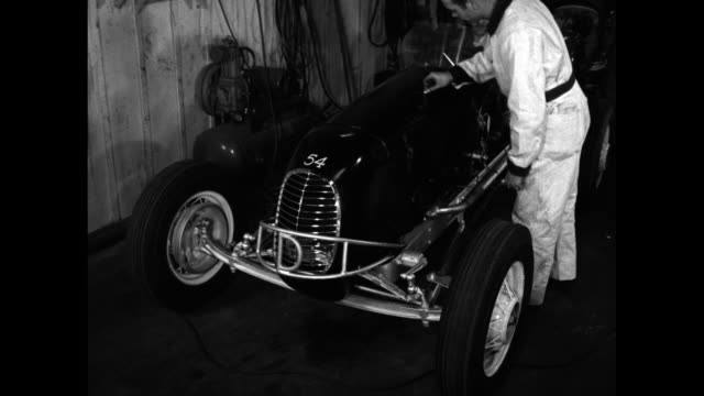 Garage with mechanics and cars in various stages of completion / man's hand writes on hood of car / the car with helmeted man is pushed by three in...
