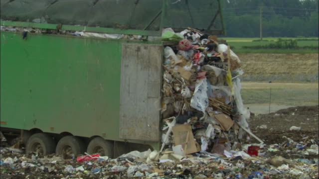 MS, Garbage falling from dump truck on landfill site, Ardley, Oxfordshire, United Kingdom